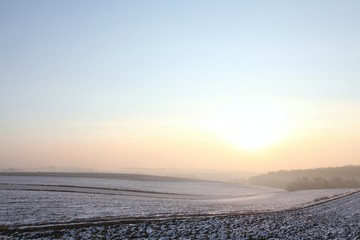 Sunrise over snow-covered field on a frosty January day