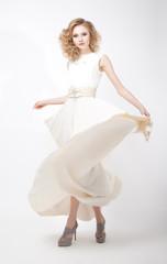Fashion style - luxurious woman in flying dress posing in studio