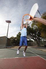 Basketball player hanging from the hoop