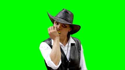 Cowboy on green background plays on harmonica harp
