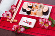 Set of sushi rolls on the white plate with flowers