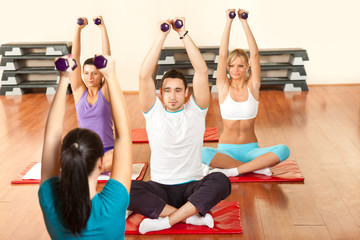 young people exercising with dumbbells