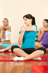 Women at the gym in a stretching class