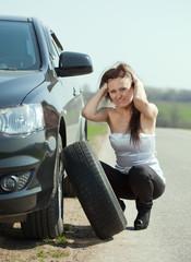 Woman changing car wheel