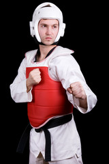 Young man in Taekwondo gear ready to fight. On black background.