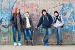 Group of smiling teenage friends posing outside