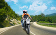 Two go on motorcycle on mountain road