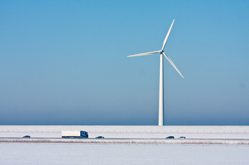 Snowy landscape with a big windturbine and a highway in front of