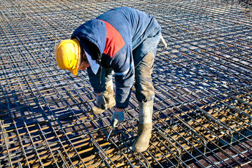 Man worker installing binding wires to reinforcement steel bars