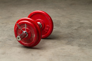 red dumbbells on a cement floor - sport concept