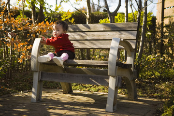 baby sitting on a park bench