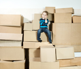 child sitting on the top of stack packed carton boxes.