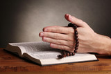 Hands holding wooden rosary over open russian holy bible