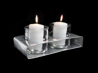 Two lit candles in a vintage zinc candle holder, isolated