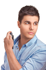 Handsome young man using perfume