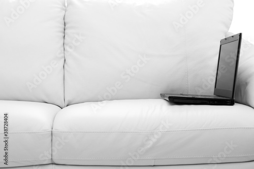 A black laptop computer on white sofa