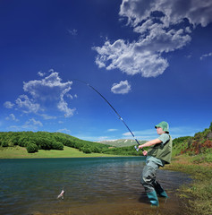 Fisherman fishing on a Mavrovo lake, Macedonia