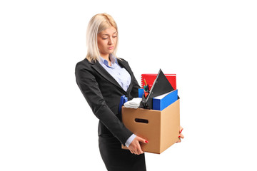 A fired businesswoman in a suit carrying a box of personal items