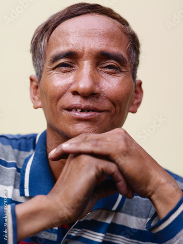 mature Asian man smiling and looking at camera