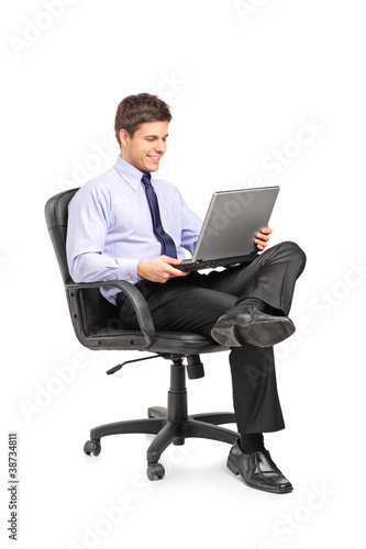 Young smiling businessman sitting in office chair and working on