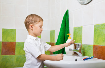 boy washes with hand soap.