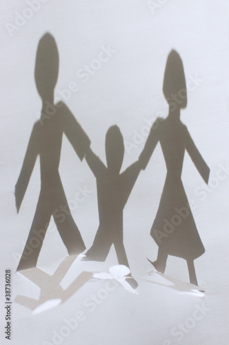 Shadow from Paper people chain: man, woman and baby. Family conc