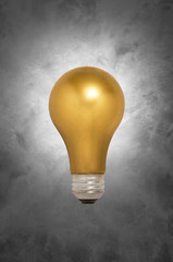 Gold Light Bulb Floating Against a Gray Background