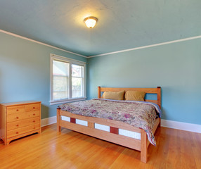 Blue bedroom with oak floor and large bed.