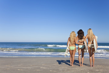 Three Beautiful Women Surfers In Bikinis With Surfboards Beach