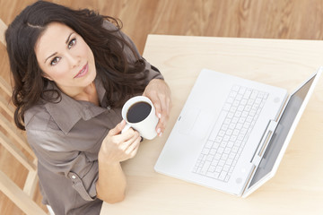 Woman Using Laptop Computer At Home Drinking Tea or Coffee