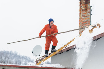 Man cleaning snow off the roof