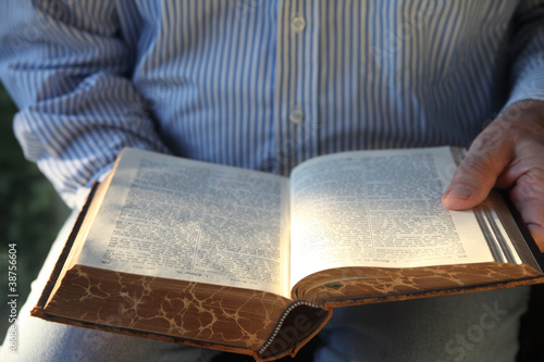 man reading 1904 German Bible in sunlight