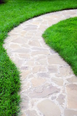 Garden path with grass growing up between the stones