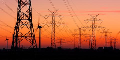 Strommasten bei Sonnenuntergang mit Windrädern