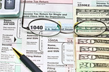 Tax forms 1040 and money.