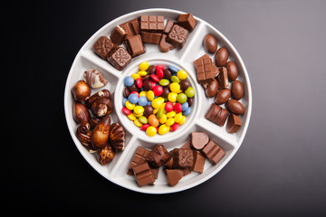 Colorful chocolate sweets with pieces of chocolate, top view