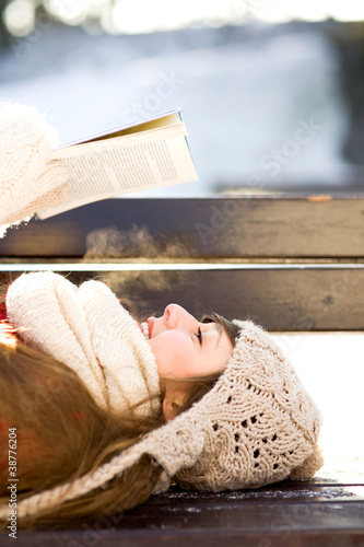 Woman reading book outdoors at winter time