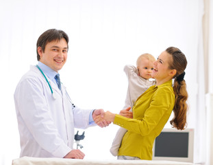 Mother thanking pediatrician doctor for baby examination