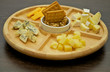 Various types of cheese on wooden plate