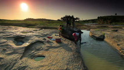Some Kids washing clothes in a river in Kenya at sunset.