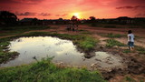 Group of boys playing at village water hole at sunset in Kenya.