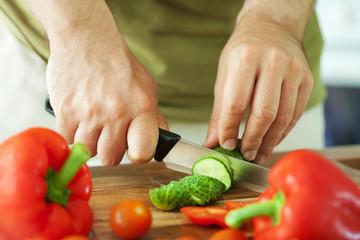 man cutting vegetables for salad