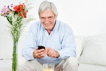 Senior auf Sofa nutzt Smartphone