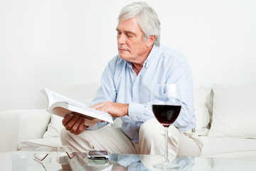 Senior liest ein Buch auf Sofa
