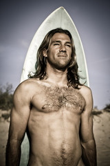 Blonde long haired muscular surfer and surfboard.