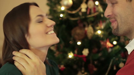 Couple talking and kissing in front of christmas tree