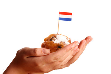 Two young hands offering a typical Dutch donut