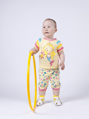 a little girl in a yellow dress posing in studio with a hula hoo