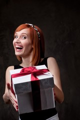 Funny redhead girl with a gift box.