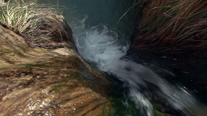 Stock Video Footage of a stream flowing over a boulder in Israel.